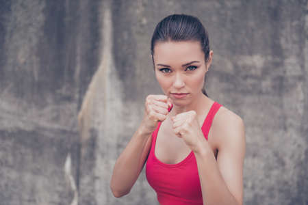Close up portrait of attractive serious fit boxer, ready for fight, on concrete wall background, wearing pink fashionable sport wear