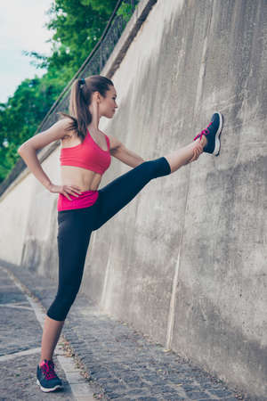Pretty young slim trainer is stretching her legs by doing exercise. She is training outdoors on a summer day, wearing fashionable sport wear, focused