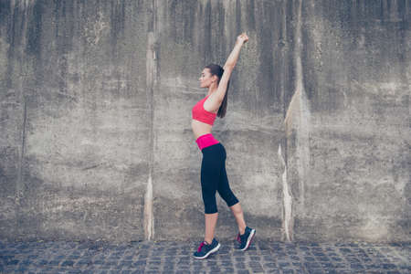 Young sportwoman trainer is making stretching outdoors in town. She is so relaxed and healthy, wearing modern pink and black sport outfit, on the concrete wall`s background