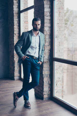 Full length of young bearded man, who is standing near the window with crossed legs and looking in camera. He is in a suit and his hands are in pockets
