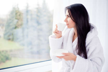 Close up side portrait of dreamy cute brunette drinking coffee. She is relaxed and looking in the window