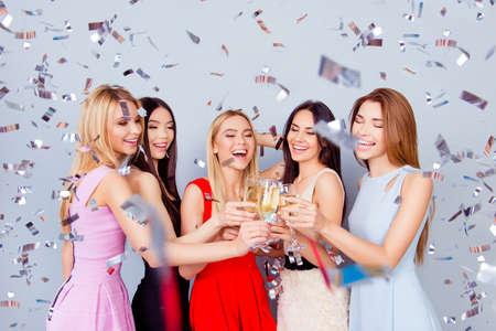 Proost op de opening van de droomplek! Vijf opgewonden vriendinnen roosteren, allemaal in kleurrijke jurken, zo schattig, charmant, feestelijk. Glanzende zilveren confetti hangt in de lucht! Verbazingwekkend Stockfoto