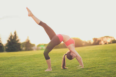Young yoga trainer is making bridge position with leg up outdoors in spring park on nice green grass, so fit and healthy, wearing modern pink and black sport outfit