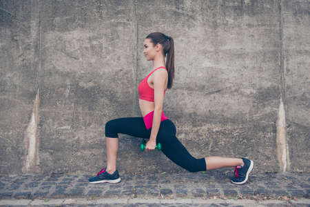 Pretty young slim trainer is stretching her legs by doing exercise, using dumb bells. She is training outdoors on a summer day, wearing fashionable sport wear, smiling