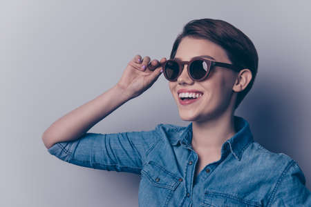 Close up portrait of glamorous young pretty girl in wooden sunglasses and stylish jeans shirt on the light blue background 스톡 콘텐츠 - 85642885