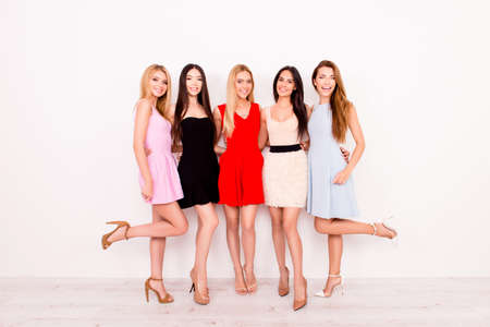 Full length of excited girlfriends in colorful short cocktail dresses are ready for birthday celebration party, charming and cute, pretty and elegant, with long nice legs in a high heels trendy shoes Stock Photo