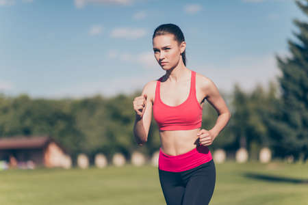 Young lady athlete is running outdoors, training for marathon run.