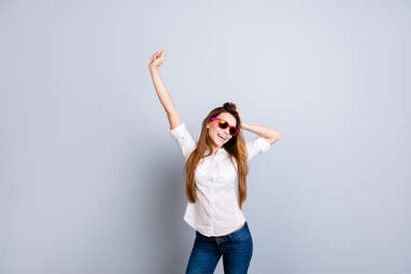 Young cheerful  attractive girl in white shirt and jeans, pink sun glasses is standing on pure grey background in pose and touch her nice hair 版權商用圖片