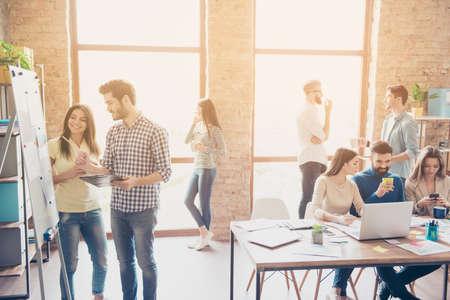 Startende partners werken in vrijetijdskleding en bespreken de ideeën voor een nieuwe ontwikkelingsstrategie op een mooie plek in de buurt van de white board flip-over in een comfortabel en gezellig licht kantoor Stockfoto - 85644140