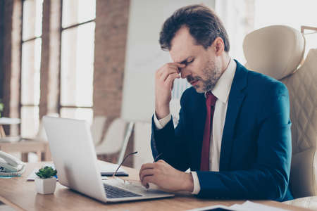 Exhausted boss is holding his nose bridge with closed eyes, he is tired and depressed. He is broker, he is wearing suit with tie and is sitting at his work place Reklamní fotografie