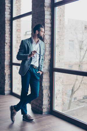 Full length of young bearded man, who is standing near the window with crossed legs and looking far. He is in a suit and holding glasses