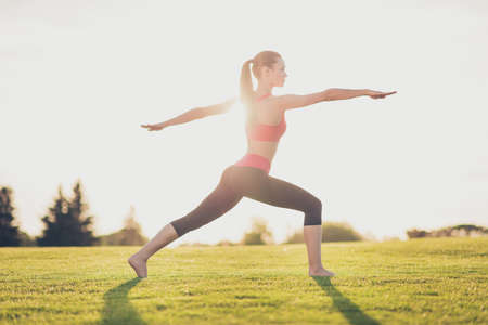 Young sport woman meditates while practicing yoga in a spring morning park.