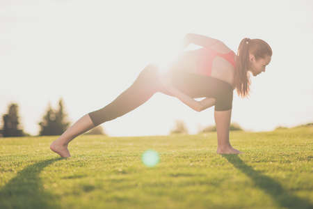 Young sporty woman is practicing yoga in the spring park outdoors in fashionable sport outfit, with tail Stock Photo