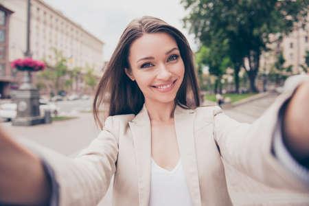 Bezaubernde junge Dame macht selfie auf einer Kamera. Sie trägt formelle Kleidung und lächelt, während sie draußen in der Stadt spazieren geht
