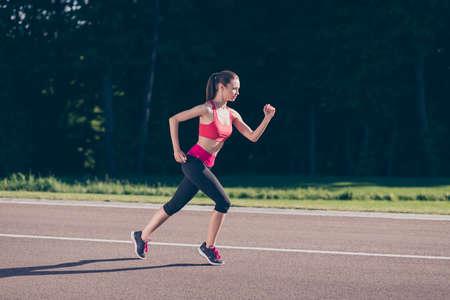 Young lady trainer running outdoors, training for marathon run. 版權商用圖片