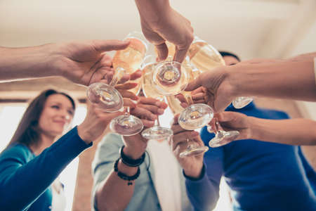 Low angle cropped photo of friends clinking the glasses of bubbling champagne to celebrate special occasion together Stock Photo
