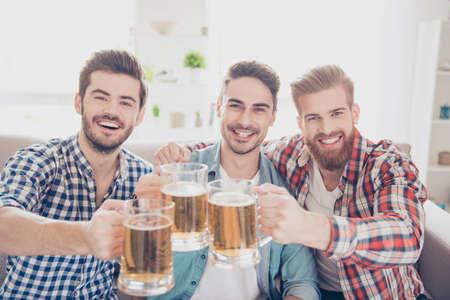 Feche acima de uma foto de três homens consideráveis felizes que comemoram vidros da vitória e do tinido da cerveja. Eles são fãs de jogos esportivos como futebol, basquete, hóquei, beisebol