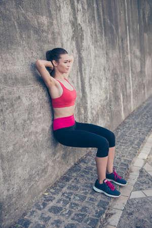 De jonge modieuze sportvrouw rekt zich op de straat op een de zomerdag uit. Ze is erg buigzaam en flexibel als gevolg van haar reguliere trainingen, het dragen van trendy sportoutfit, sneakers Stockfoto - 85642643
