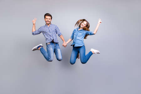 Cheerful and playful couple in casual outfits are jumping and gesturing peace signs indoors, smiling, posing