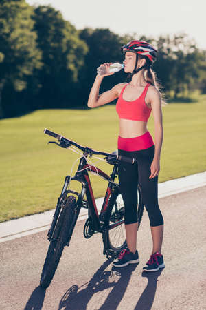 Young fit sportwoman is drinking water to refresh. She is outside on a summer day cicling on modern bike