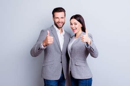 灰色の背景に親指を表示するフォーマルな摩耗で2つの笑顔の幸せなビジネスの人々