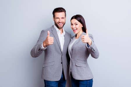 Two smiling happy business people in formal wear showing thumbs-up on gray background