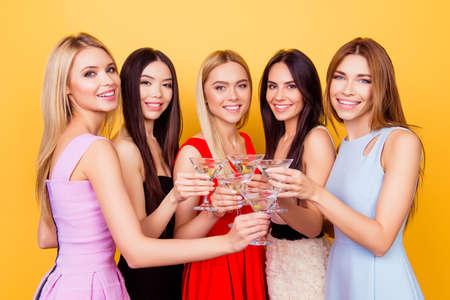 Vier schattige bruidsmeisjes en een toekomstige bruid roosteren op het vrijgezellenfeest, allemaal in kleurrijke cocktailoutfits, zo charmant, aantrekkelijk, feestelijk, luxueus en opgewonden