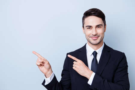 Young cheerful successful brunette lawyer on the pure light blue background is smiling, wearing suit with tie and is pointing on a copyspace with his fingers