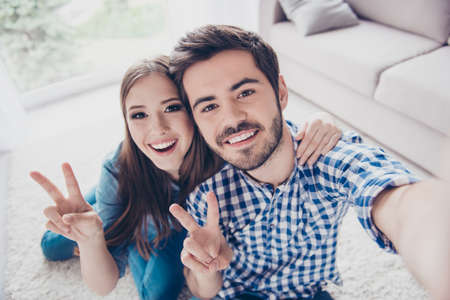 Cheerful playful sister and brother are taking selfie and showing peace signs. They are at home indoors, in casual outfits. They both have beaming smiles