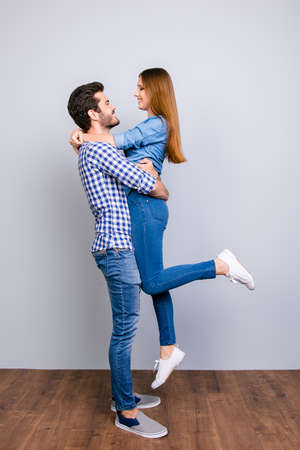 Full length portrait of dreamy happy young couple in love, they are posing, wearing casual outfits, embracing and smiling on the pure background Stok Fotoğraf