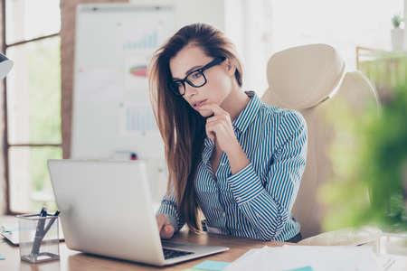 Sluit omhoog portret van de ernstige jonge bedrijfsdameconoom in formele slijtage en met glazen, zittend bij haar werkplek en geconcentreerd op het werk