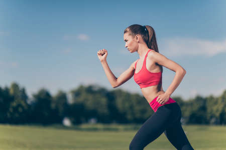 Profile cropped photo of young lady athlete, running outdoors, training for marathon run, in fasionable sports outfit, so focused, fit and fast! 版權商用圖片