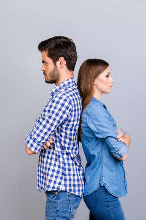 Annoyed couple is ignoring each other, standing back to back, wearing casual clothes, with crossed hands on the pure background