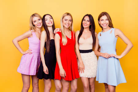 Vijf schattige dames in kleurrijke korte cocktailjurken zijn klaar voor een avondje uit