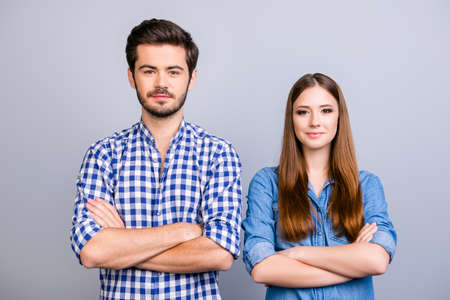 Two cheerful young lovers are looking at the camera and smile, standing both with crossed hands, wearing casual clothes, on the pure background