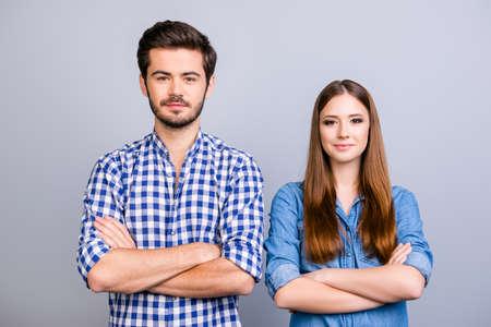 Due allegri giovani innamorati guardano la telecamera e sorridono, entrambi con le mani incrociate, vestiti casual, sullo sfondo puro Archivio Fotografico - 85777665