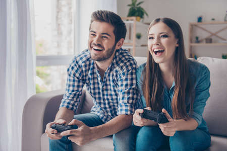 family sofa: Excited funny friends, playing video games at home, sitting on sofa and enjoying themselves. They have great weekend in nice company indoors Stock Photo