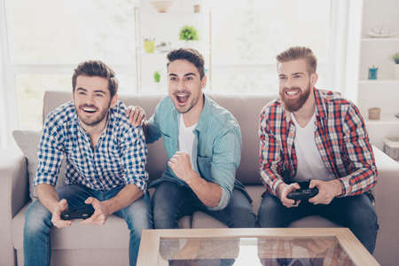 Yes! Our team is winning! Competition of guys playing car race. Three excited friends are playing games indoors, sitting on cozy beige sofa and enjoying themselves. They have great and fun time Foto de archivo
