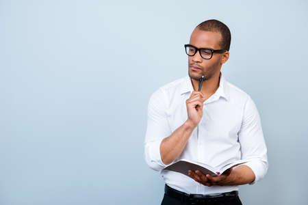 オタク的なアフリカの教授は思慮深い, 眼鏡で, ノートを保持し、試験について考える