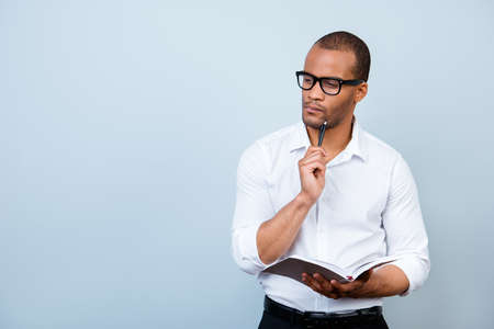 Nerdy academic african professor is thoughtful, in glasses, holding a notebook and thinking about exams