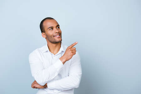 Young handsome mulatto banker on the pure light blue background is pointing on a copyspace with his finger, wearing white strict shirt Stock Photo