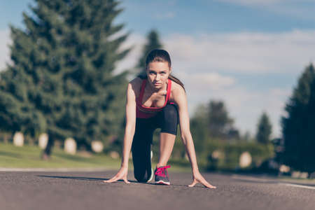 Close up low angle photo of young lady athlete, training for marathon run. Beautiful fitness model, in fashionable sports outfit, so focused, fit and attractive