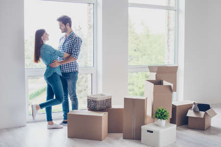moving box: Happy young couple moved to new place to start live together, they are embracing, around many carton boxes with their things. The room is very light and bright, they are wearing casual outfit Stock Photo