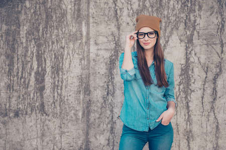Hot attractive young girl is standing on the concrete wall`s background outdoors, fixing her glasses. She is wearing casual jeans outfit and brown hat