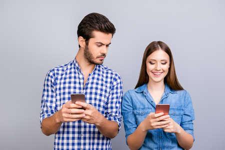 호기심 많은 남자 친구가 그의 애인의 스마트 폰을 감시하고있다. 그들은 캐주얼 셔츠를 입고, 순수한 배경에 고립 된 서있다.