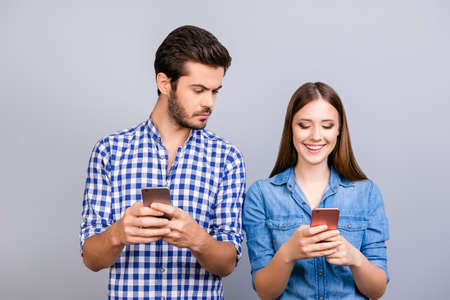 Curious boyfriend is spying his lover`s smartphone. They are wearing casual shirts, standing isolated on pure background