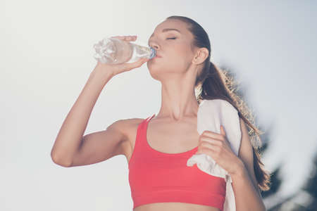 Close up low angle photo of young fit sportwoman, she finished her work out and now drinking water to refresh. She is outside on a summer stadium, with a towel