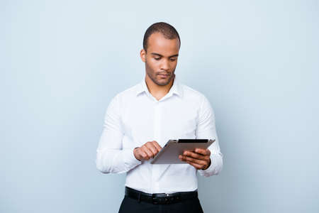 Successful ponder young african guy is browsing at his tablet, standing on the pure background
