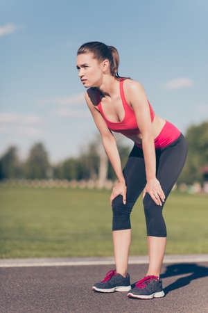 Young lady athlete is training for marathon run. Beautiful fitness model, in fasionable sports outfit, outdoors in a summer stadium, so focused, fit and attractive 版權商用圖片