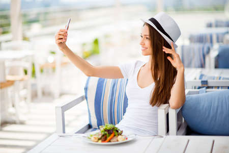 Profile photo of young lady, having lunch on a summer open air light terrace outdoors. She is in a casual wear, having salad and taking selfie with her pda, fixing hat